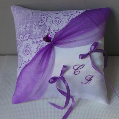 Un joli coussin pour alliances drapé violet, dentelle blanche